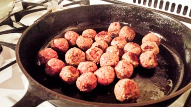 Meatballs, being fried in olive oil