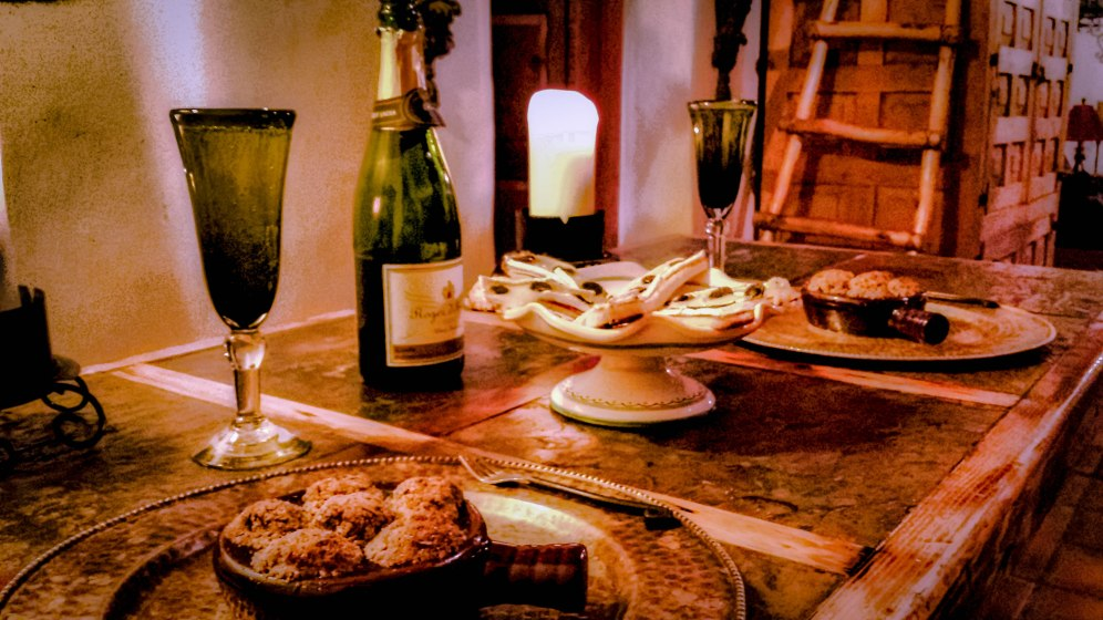 A dinner view of Escargots à la Provençale, accompanied by French bread topped with triple-creme brie and black truffles, with a brilliant cava alongside