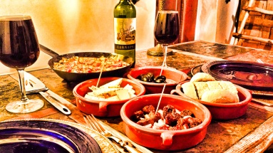 Dinner view of Tortilla Española with manchego cheese, Spanish chorizo, olives and crusty bread, accompanied by a hearty Spanish red wine