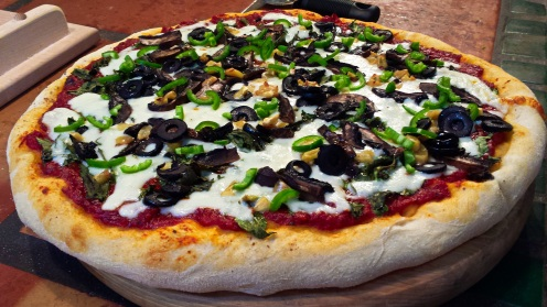 Pizza with portabella mushrooms, large ripe black olives, roasted garlic slices and fresh jalapeno peppers
