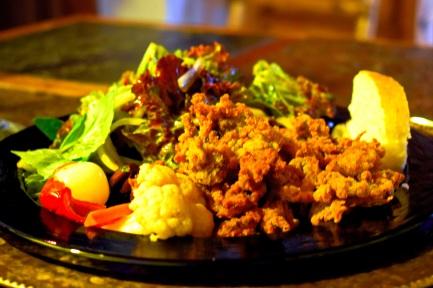 Dinner plate view of crispy fried calamari with fresh green salad and giardiniera