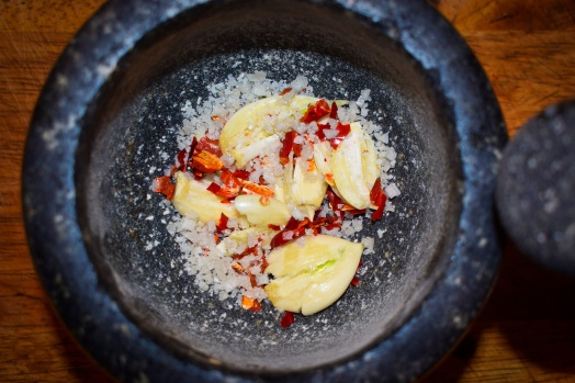 Fresh garlic, dried spicy red chiles and coarse salt are ground together in a mortar & pestle to form the paste which will accent our Brazilian-style grilled steaks