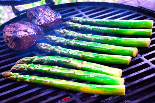 Giant asparagus spears grilling over wood alongside the sirloin steaks