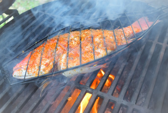 Grillng red snapper over olive wood fire